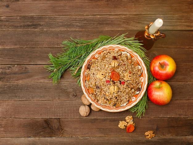Piatto della tradizionale tradizione slava alla vigilia di natale. rami di pino, mele, noci e candela.