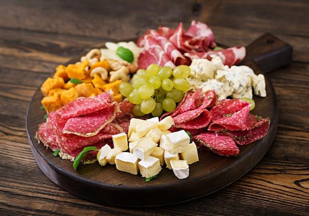 Piatto di antipasti con pancetta, salumi, salsiccia, formaggio blu e uva