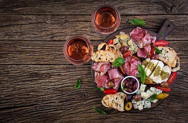Piatto di antipasti con prosciutto, prosciutto, salame, gorgonzola, mozzarella con pesto e olive. vista dall'alto, dall'alto
