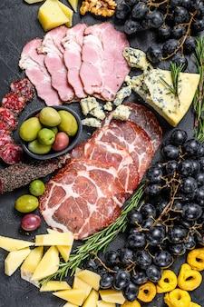 Piatto di antipasti con prosciutto, prosciutto, salame, gorgonzola, mozzarella e olive. sfondo nero. vista dall'alto
