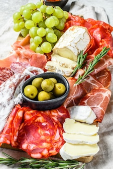 Piatto di antipasti di carne fredda con uva, prosciutto, fette di prosciutto, carne secca, salame di chorizo, fuet, camembert e formaggio di capra. vista dall'alto.