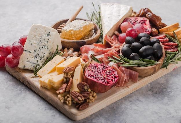 Piatto di antipasti italiani tradizionali. formaggi assortiti sul tagliere di legno. brie, fette di cheddar, gogonzola, noci, uva, olive, prosciutto, rosmarino e bicchiere di vino rosso. vista dall'alto