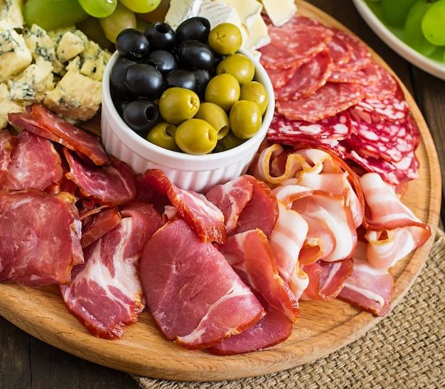 Piatto di antipasto con pancetta, scatti, salame, formaggio e uva su un tavolo di legno
