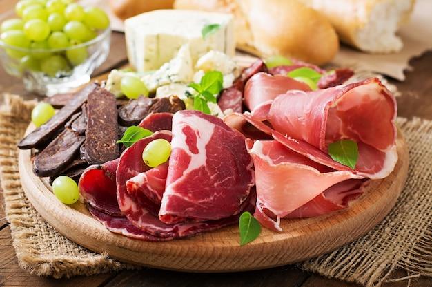 Piatto di antipasto con pancetta, scatti, salsiccia, gorgonzola e uva su un fondo di legno