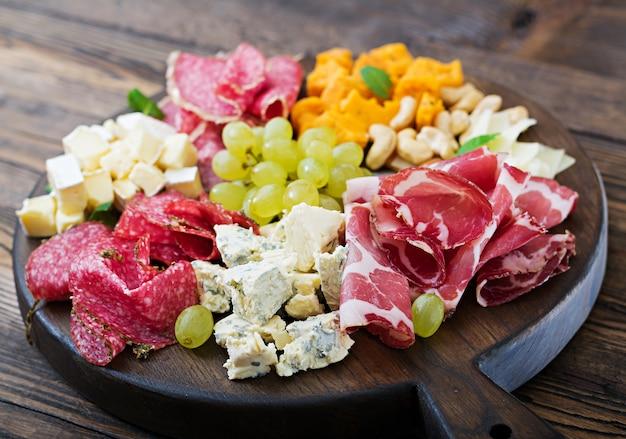 Piatto di antipasto con pancetta, scatti, salsiccia, gorgonzola e uva su un tavolo di legno.