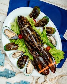 Piatto di aragosta e cozze crudo guarnito con lattuga e pomodorini