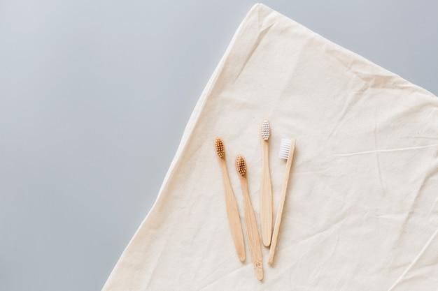 Piatto di bambù naturale eco spazzolini da denti giaceva su sfondo grigio. concetto di stile di vita sostenibile. zero rifiuti, articoli senza plastica. fermare l'inquinamento da plastica.