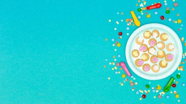 Piatto di biscotti circondato da palloncini e coriandoli