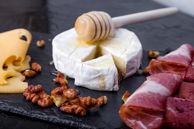 Piatto di carne e formaggio con le noci sulla superficie nera del piatto dell'ardesia