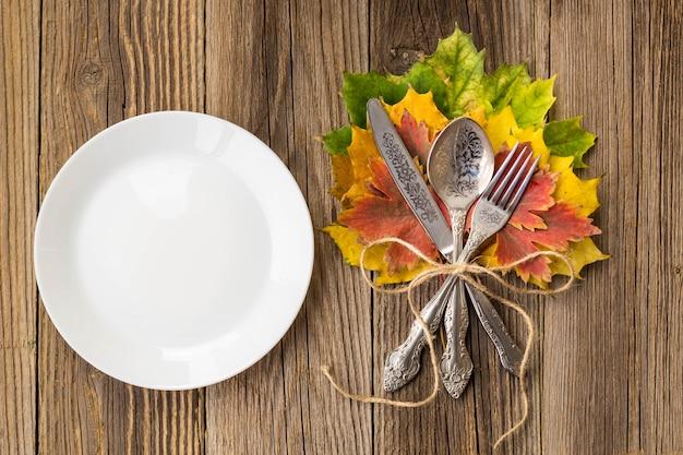 Piatto di cena del ringraziamento con forchetta, coltello e foglie di autunno sul tavolo di legno rustico. vista dall'alto, copia spazio