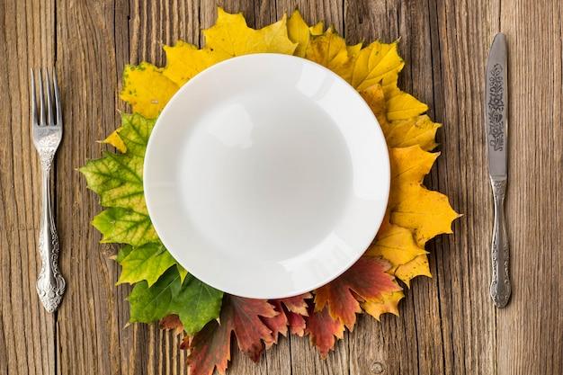 Piatto di cena del ringraziamento con forchetta, coltello e foglie di autunno sul tavolo di legno rustico