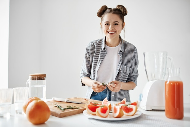 Piatto di decorazione sorridente della ragazza graziosa per la prima colazione con il pompelmo affettato e rosmarini sopra la parete bianca. frullato disintossicante rinfrescante.