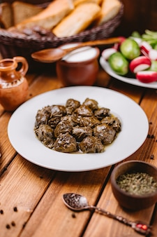 Piatto di dolma di foglie di vite azera servito con yogurt e insalata