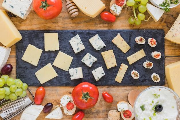 Piatto di fetta di formaggio sul bordo di ardesia nera sopra il tavolo