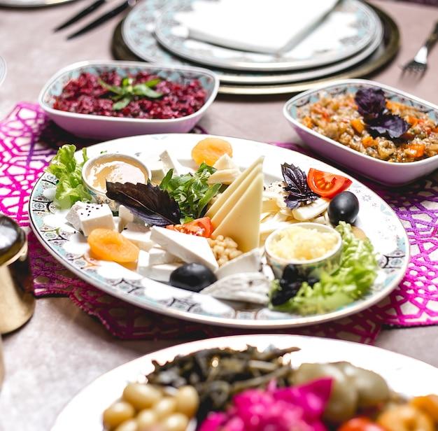 Piatto di formaggi assortiti vista laterale con erbe di miele e olive con albicocche secche