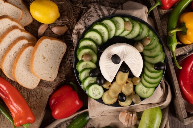 Piatto di formaggi, cetrioli e olive con fette di pane bianco. vista dall'alto