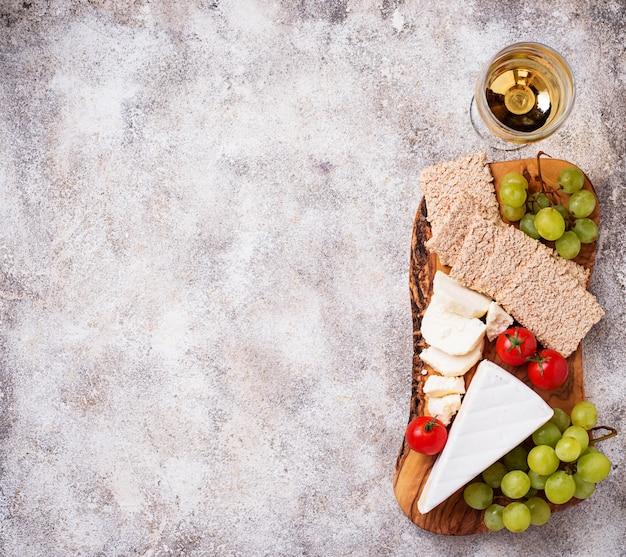 Piatto di formaggi con brie, uva e vino