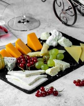 Piatto di formaggi con cheddar blue di capra e formaggio bianco parmigiano e uva