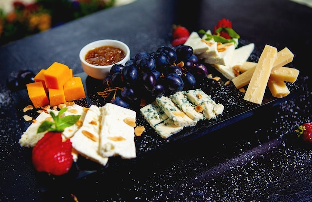 Piatto di formaggi con cubetti di formaggio cheddar, formaggio bianco, bastoncini di parmigiano, gorgonzola e uva