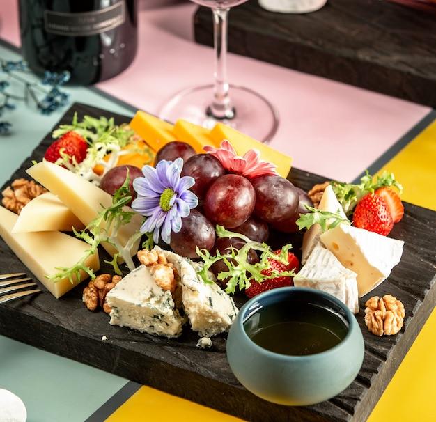 Piatto di formaggi con formaggio cheddar, capra, gouda, gorgonzola, miele, uva e fiori