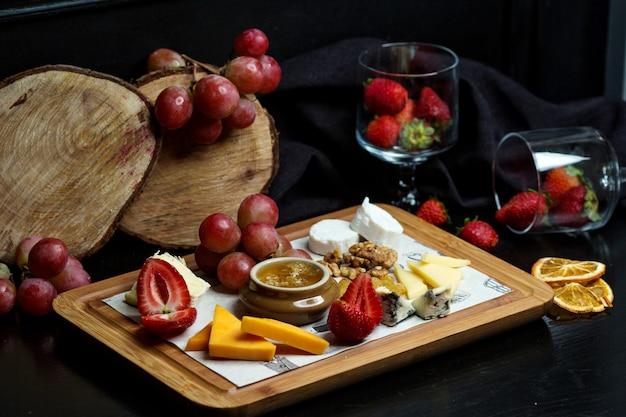 Piatto di formaggi con formaggio cheddar, formaggio bianco e gouda, fragola, miele, noci e uva