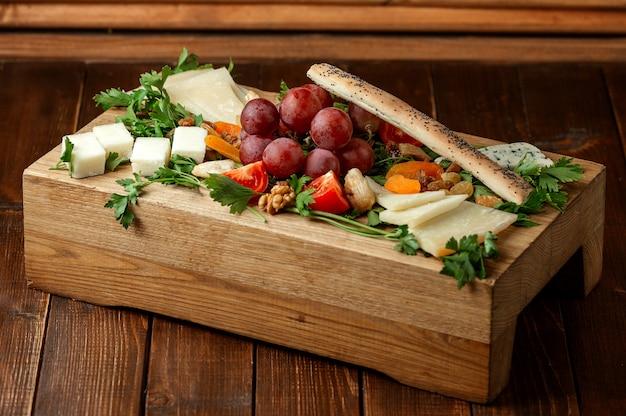 Piatto di formaggi con frutti sul tavolo