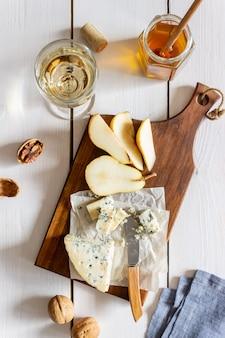 Piatto di formaggi con gorgonzola e pera. merenda al vino. cucina italiana. cibo vegetariano. mangiare sano.