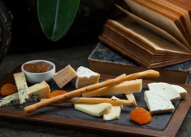 Piatto di formaggi con marmellata, frutta secca e galetta