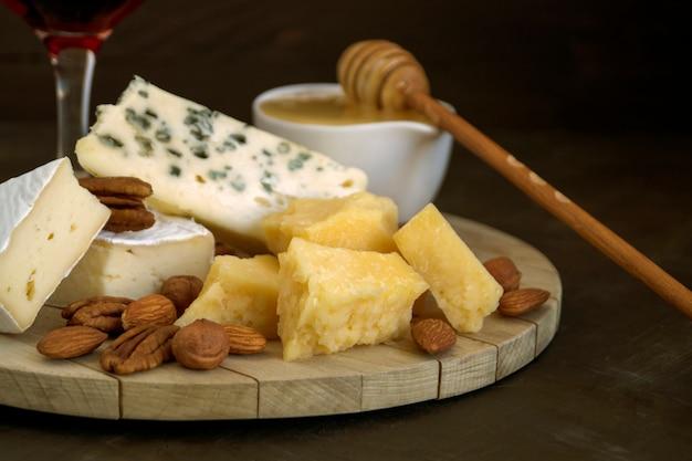 Piatto di formaggi con noci e miele su sfondo scuro.