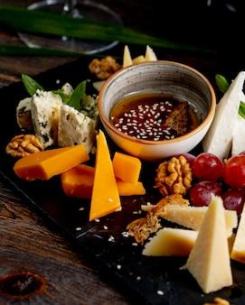 Piatto di formaggi con noci uva e salsa