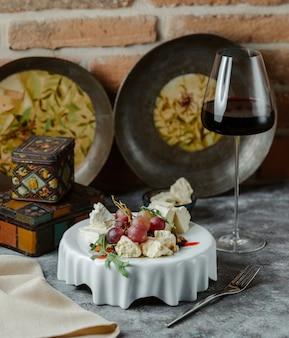 Piatto di formaggi con uva e un bicchiere di vino rosso
