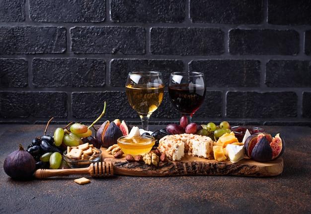 Piatto di formaggi con uva e vino