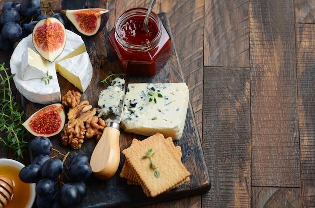Piatto di formaggi con uva, fichi, cracker, miele, gelatina di prugne, timo e noci.