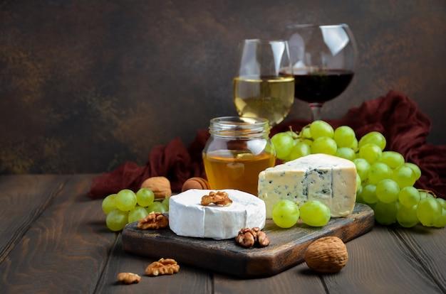 Piatto di formaggi con uva, miele e noci su sfondo scuro.