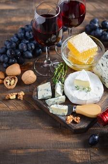 Piatto di formaggi con uva, miele, noci e vino rosso su un tavolo di legno