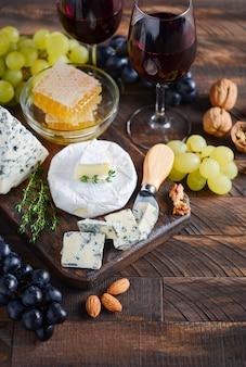 Piatto di formaggi con uva, miele, noci e vino rosso
