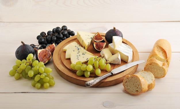 Piatto di formaggi con vari tipi di formaggi e fichi e uva su una superficie di legno bianca