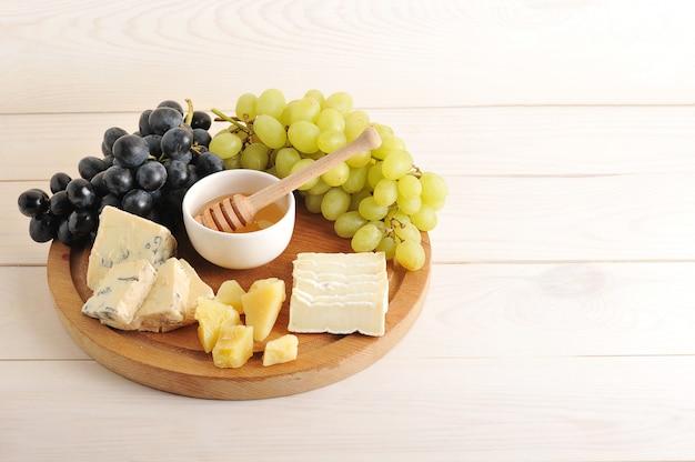 Piatto di formaggi con vari tipi di formaggio, uva verde e nera, miele