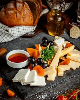 Piatto di formaggi con winegrape e fette di pesca
