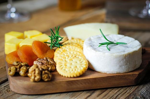 Piatto di formaggi, formaggio camembert, rosmarino, cracker, albicocca secca e noci