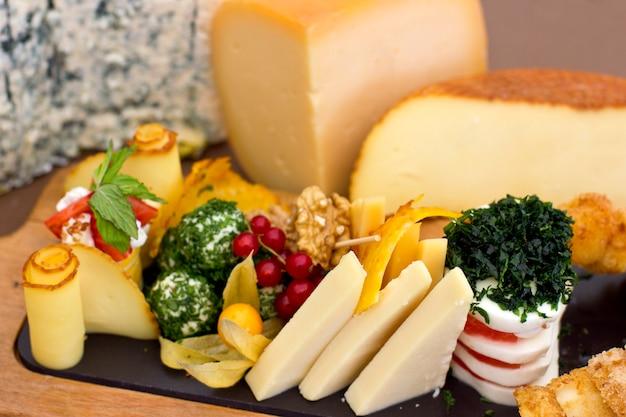 Piatto di formaggi: roquefort con stampo blu, formaggio cheddar, formaggio affumicato, mozzarella su tavola di legno.