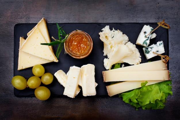 Piatto di formaggi servito con uva e marmellata. una squisita natura morta di vari formaggi con marmellata e uva sul buio