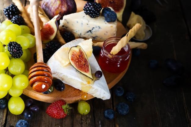 Piatto di formaggi servito con vino, marmellata e stick con miele
