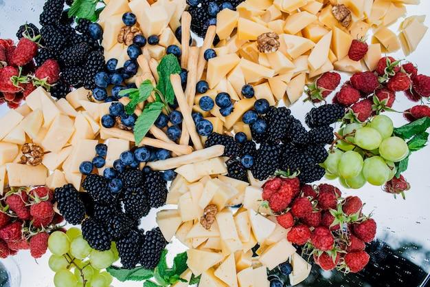 Piatto di formaggi servito con vino, uva, prosciutto, olive, snack table, marmellata e miele
