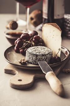 Piatto di formaggio e vino rosso con frutta e noci