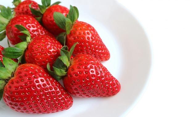 Piatto di fragole mature rosse fresche vibranti isolate su fondo bianco con spazio libero per testo e progettazione