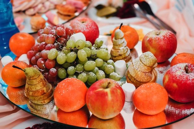 Piatto di frutta di pere, mele, mandarini e uva per una sana dieta vegetariana