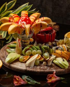 Piatto di frutta fresca con un gelato in salsa rossa in cima