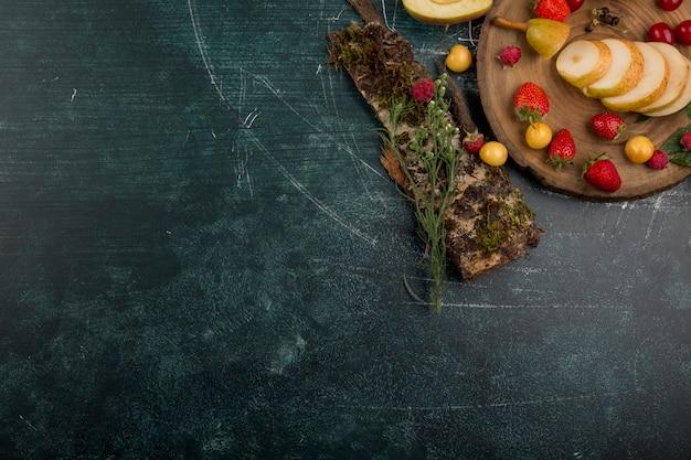 Piatto di frutta rotondo con pere, mele e frutti di bosco isolati su sfondo blu nell'angolo
