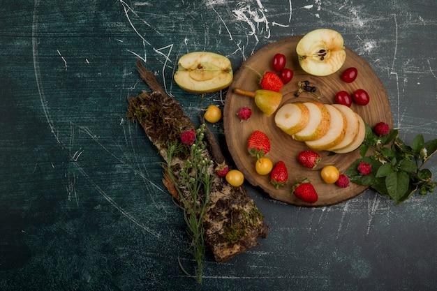 Piatto di frutta rotondo con pere, mele e frutti di bosco isolati su sfondo blu, vista dall'alto